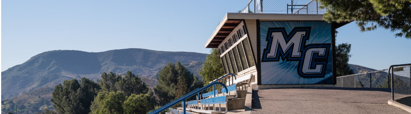 photo of Moorpark College logo on side of score booth with mountain in the background