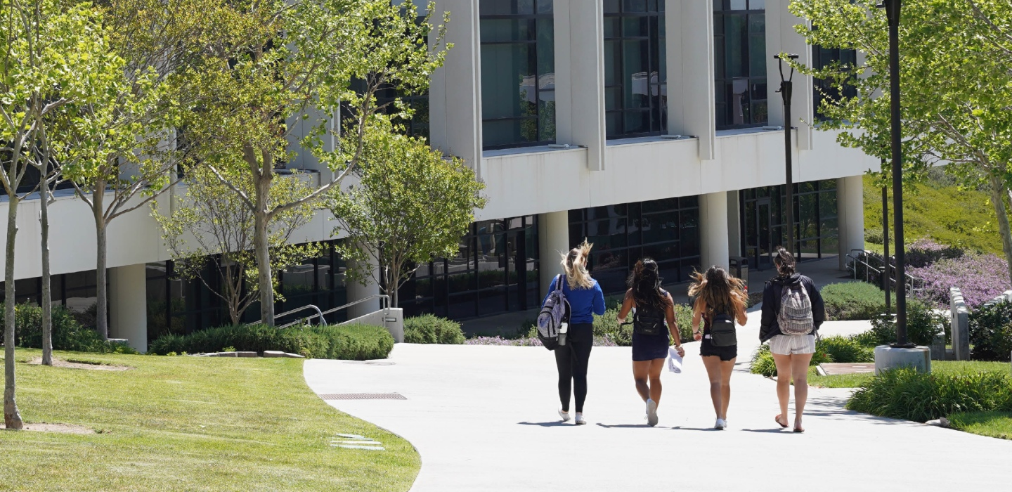 students walking past academic center building