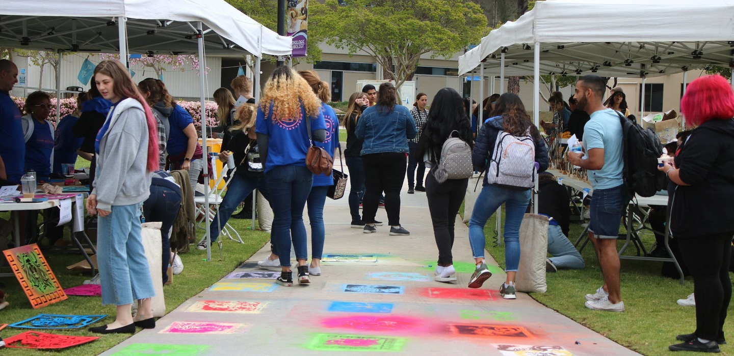 Students stop by booths at an outdoor fair on campus.