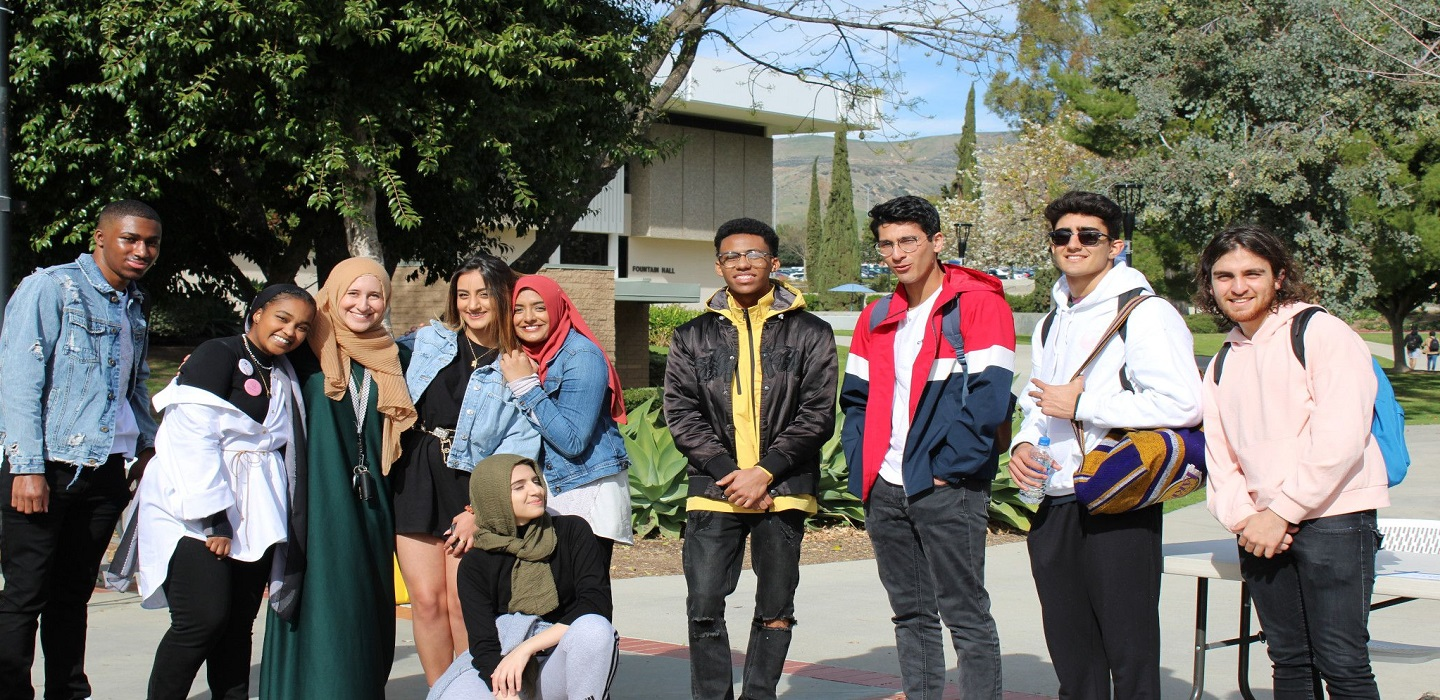 Students from campus clubs pose for a picture along Raider Walk.