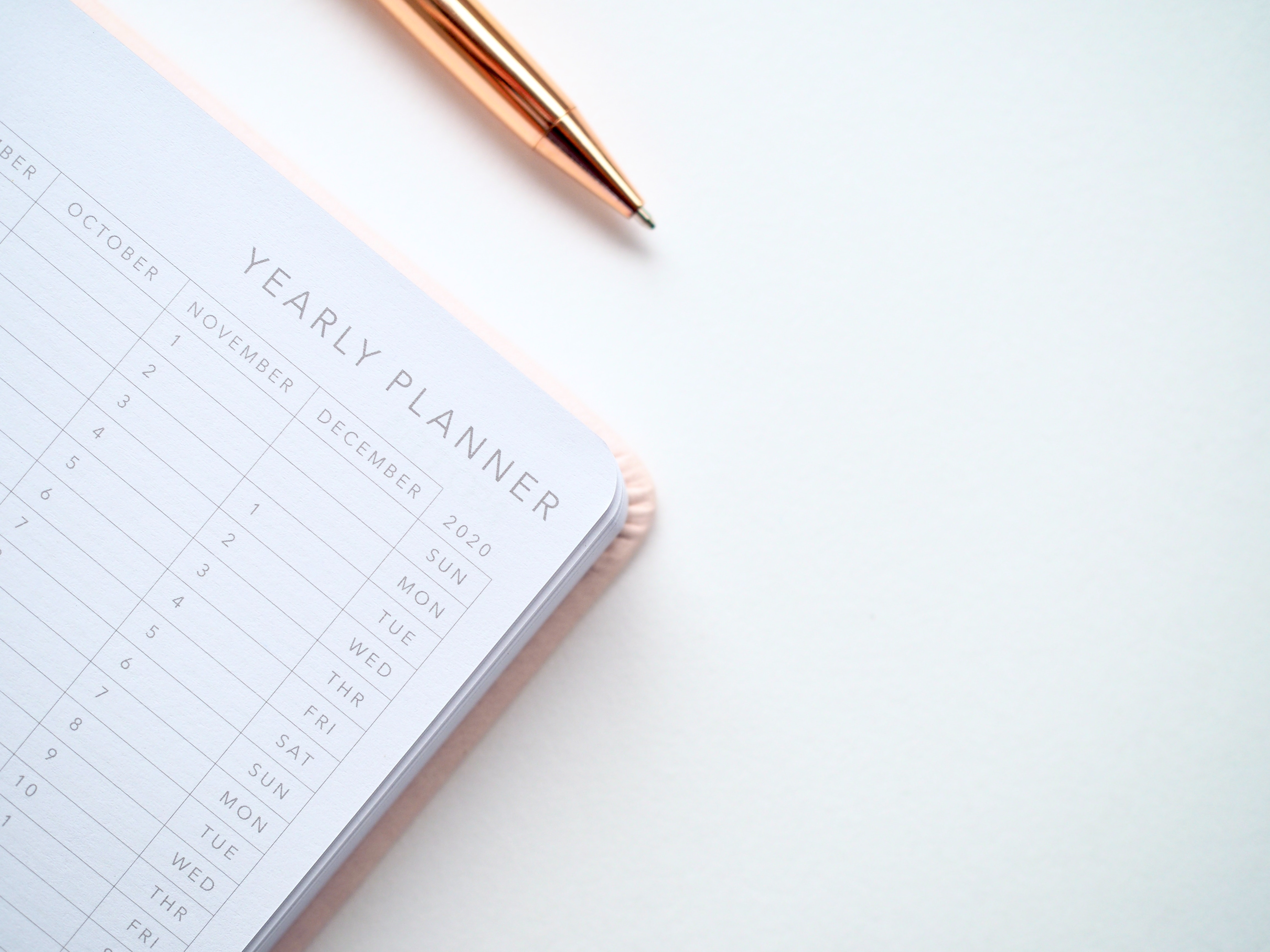 Yearly planner on a table with a rose gold pen