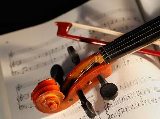 The top of a violin and bow laying across a sheet of music.