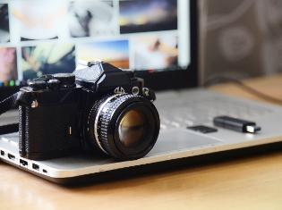 a digital camera and a flash drive sitting on top of a laptop.