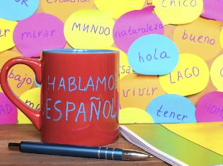 Post it notes and a coffee mug that have spanish words written on them.