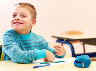 A young child smiling at a school desk while writing.