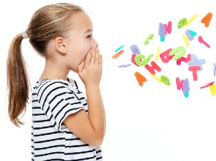 A small child holding their hands to their face and toy letters falling in front of them.