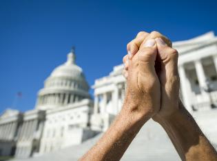 Hands clasped together in front of a capital building.