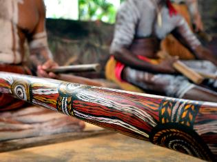 A wooden tool with decorative tribal markings.