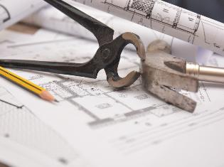 A hammer, a pencil, and other tools sitting on top of building blueprints.