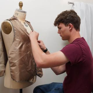 male student sewing a costume